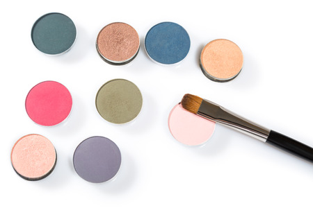Isolated close up of blue, red, green, white and grey eye shadow colors and three brushes against white background Stock Photo