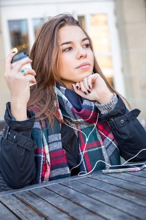 Young girl enjoying coffee with her music as she sits at a table at an open-air restaurant listening to tunes on her mobile phone
