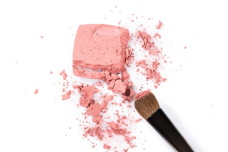grooming product: Close up High angle view of broken pink cosmetic powder with thick tipped brush against a white background
