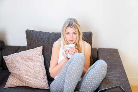 Single blond young adult woman in gray polka dot tights holding mug while curled up on sofa chair