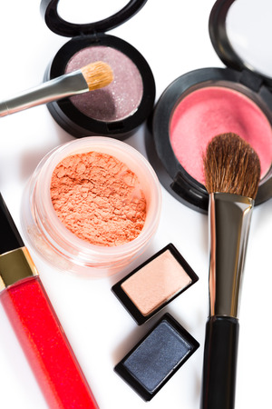 grooming product: Diverse selection of brushes along side makeup powders, eye shadow, red and pink lipsticks and compact with foundation