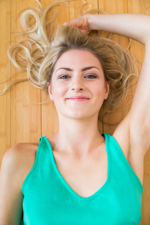 High angle view on cute smiling blond young adult woman in green shirt laying down on hardwood floor