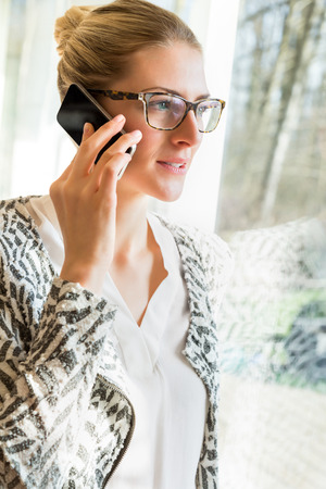 using voice: Happy woman in eyeglasses using cell phone to talk or check voice mail while standing in sunlight