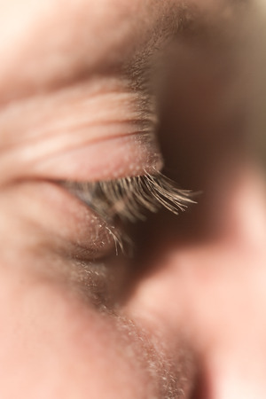 Extreme Anatomy Close Up of Male Face with Blond Eyelashes and Focus on Down Cast Eye, Illuminated in Bright Lighting