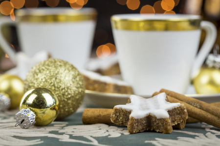 coffeebreak: Two stylish cups of coffee with spicy star shaped Christmas cookies with white glazing arranged in a festive still life with baubles, cinnamon and star anise spices, background party light bokeh