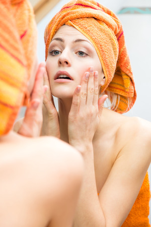 rejuvenated: Attractive woman wrapped in towel touching the sides of her face with big happy smile in reflection on mirror Stock Photo