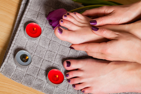 uñas pintadas: Cerca de la mujer con pedicura y manicura hecho en un precioso profundas velas encendidas junto púrpuras y tulipán fresca Foto de archivo