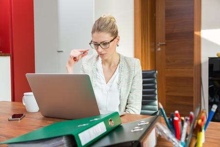 trabajando en computadora: La mujer rubia joven preocupante que solo con la expresión ansiosa de trabajar juntos en la mesa llena de bloc de notas y bolígrafos