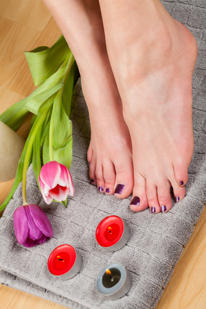 uñas pintadas: Close up of woman with pedicure and manicure done in a lovely deep purple beside lit candles and fresh tulip