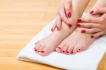 uñas pintadas: Cerrar hasta en las uñas perfectamente pintadas en los pies femeninos con la flor púrpura entre ellos sobre una toalla blanca Foto de archivo