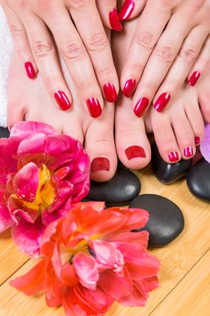 painted toenails: Pair of petite light skinned female feet on soft towel roll with beautiful pink flower near ankle over hardwood floor
