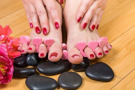 toenail: Close up of pink foam spacers between pretty toes with red toenail paint on top of smooth black massage stones and hardwood floor Stock Photo