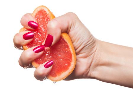 uñas pintadas: Mujer mostrando sus uñas cuidadas con un color rojo moderna viva de exprimir una naranja jugosa fresca con gotas en sus dedos Foto de archivo
