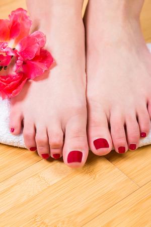 uñas pintadas: Par de luz pequeña de piel pies femeninos en el rollo de toalla suave con la flor rosada hermosa cerca de tobillo sobre suelo de madera dura