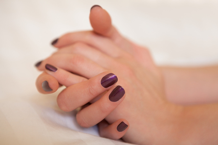 Two female hands in elegant pose with purple painted nails on grey surface