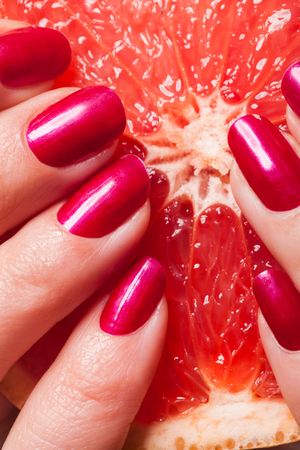 Woman displaying her manicured fingernails painted with a vivid modern shade of red squeezing a fresh juicy orange with drips on her fingers Stock Photo