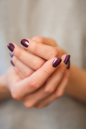 grey nails: Two female hands in elegant pose with purple painted nails on grey surface