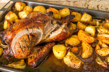 roasting pan: Delicious crispy browned roast duck with potatoes and traditional orange and apple trimmings in an oven roasting pan, close up view Stock Photo