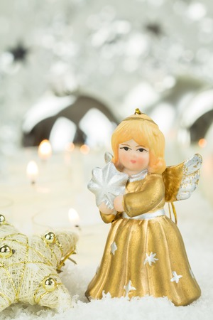the next life: Festive Still Life of Golden Angel Figurine Next to Gold Stars on Snowy Surface with Burning Candles in Background with Copy Space Stock Photo