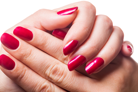 Graceful hands of a woman with red painted manicured nails in a close up view isolated on white Stock Photo