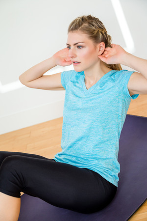 limbering: Cute young woman stretching hamstring muscles while seated on purple exercise mat indoors on hardwood floor