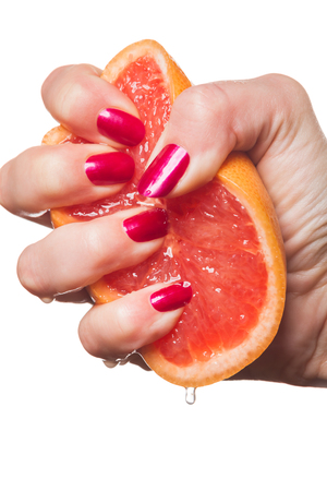 painted toenails: Woman displaying her manicured fingernails painted with a vivid modern shade of red squeezing a fresh juicy orange with drips on her fingers Stock Photo