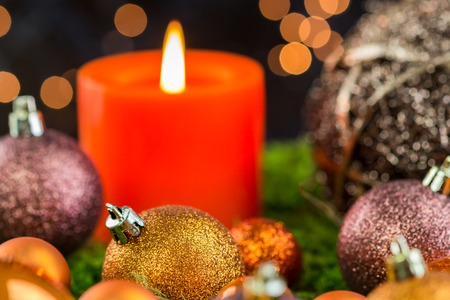 Burning red advent candle with brown and coppery themed Christmas baubles and a sparkling bokeh of party lights in the background for a festive seasonal celebration Stock Photo