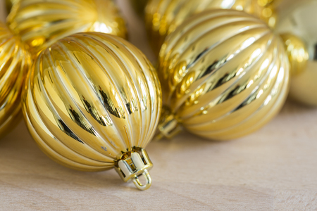 ridged: Christmas background with decorative fluted metallic gold bauble and a burning tea light candle with shallow dof and copy space for your seasonal greeting