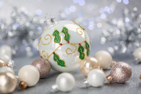 White and silver Christmas ornaments with larger globe covered with star shapes formed from glitter Stock Photo