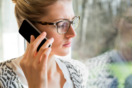 woman in eyeglasses using cell phone to talk or check voice mail while standing in sunlight
