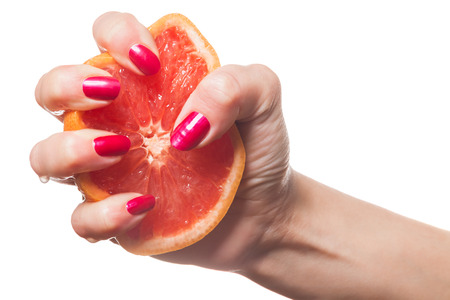 uñas pintadas: Woman displaying her manicured fingernails painted with a vivid modern shade of red squeezing a fresh juicy orange with drips on her fingers Foto de archivo
