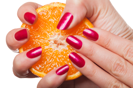 enamel: Woman with manicured red nails holding a halved fresh juicy orange in her hand in a close up view in a beauty and makeup concept