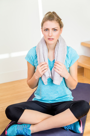 Cute young blond woman in sportswear sitting on a yoga mat portrait Stock Photo
