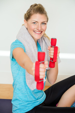 Happy young woman in blue shirt and black pants seated on purple yoga mat while lifting small dumbbell weight