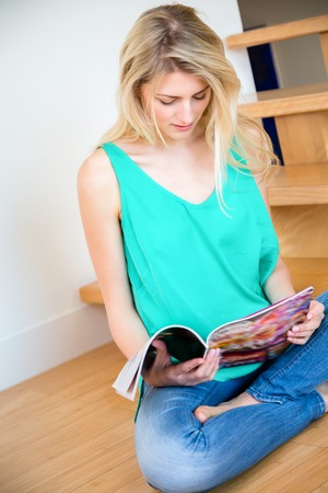 Single cute young long haired blond woman in blue jeans sitting on floor reading something near staircase