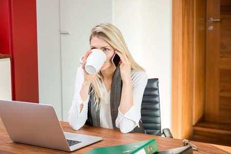 Business person drinking and using phone in front of open laptop computer at work for concept about multitasking and productivity