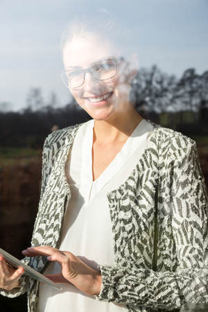 Single professional woman looking through glass with tree reflections while using tablet computer