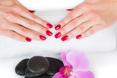 Spa theme portraying pair of female hands with nail polish on towel beside black stones and purple iris flower on white background Stock Photo