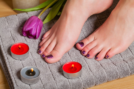 Close up of woman with pedicure and manicure done in a lovely deep purple beside lit candles and fresh tulip