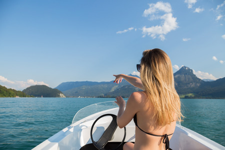 Happy friendly attractive slender young woman enjoying a boating trip on a lake in her bikini as she perches on the prow of the boat on a hot sunny summer day 版權商用圖片