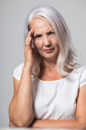 Attractive grey haired woman in her fifties suffering from a headache or migraine frowning in pain as she rubs her throbbing temples