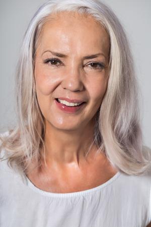 웃음과 렌즈에 직접 찾고 어깨 길이 회색 머리와 매력적인 젊은 50 세의 여자
