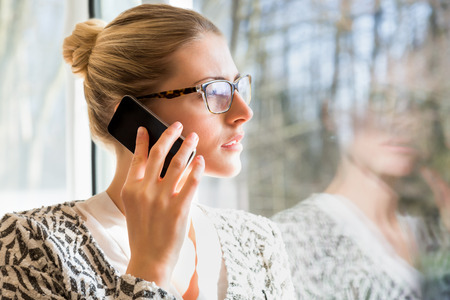 Happy woman in eyeglasses using cell phone to talk or check voice mail while standing in sunlight