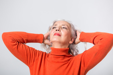 Attractive woman in her fifties wearing a red polo neck sweater relaxing with her memories tilting her head back with her hands in her hair with a faraway relaxed expression, head and shoulder on grey Stock Photo