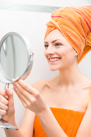 Concerned woman wrapped in orange colored towel looking at herself in round hand held mirror