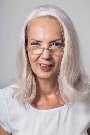 speculative: Earnest grey haired woman wearing reading glasses peering over the top with an intent look, head and shoulders on grey with copy space