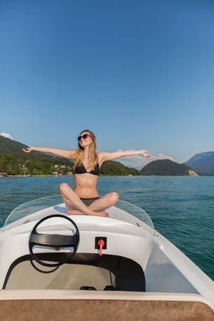 Happy exuberant young woman celebrating the sun as she sits cross legged on a motorboat on a calm lake with her arms outstretched and a smile of bliss