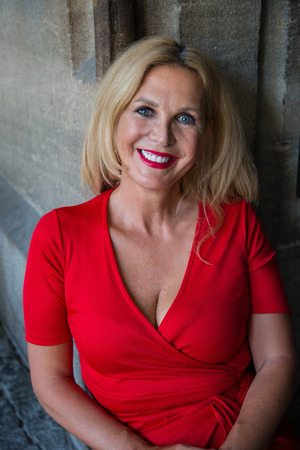 Outdoor portrait of mature blonde long-haired smiling woman wearing red dress Banco de Imagens