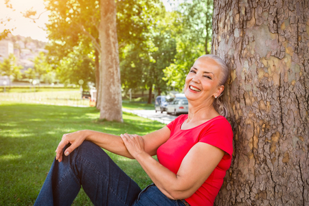 leaning against: Relaxed attractive woman with a lovely smile sitting on the grass in a park leaning against a tree in the shade in warm glowing sunshine