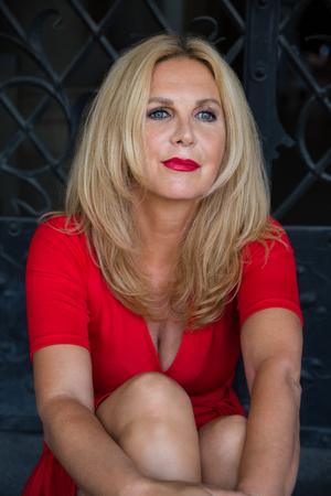 屋外に座っている間赤いドレスを着ている長髪のブロンドの熟女の肖像 写真素材